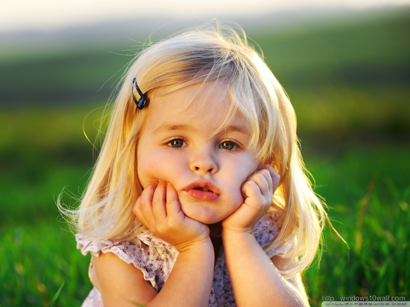 Sweet Baby Girl with Hands on Face Background Wallpaper